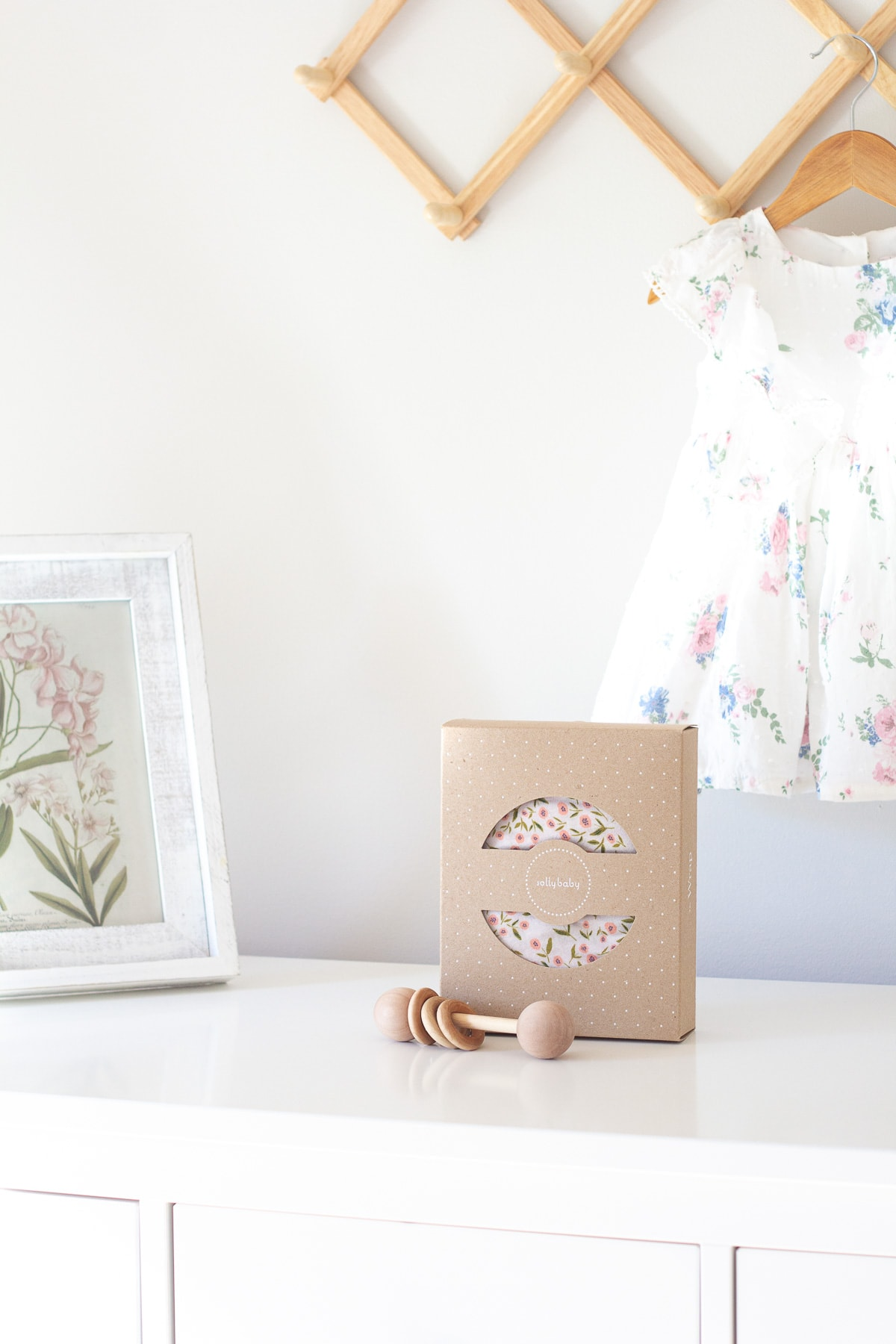 A Solly Baby Wrap on a white dresser with an heirloom wooden rattle in front of it.