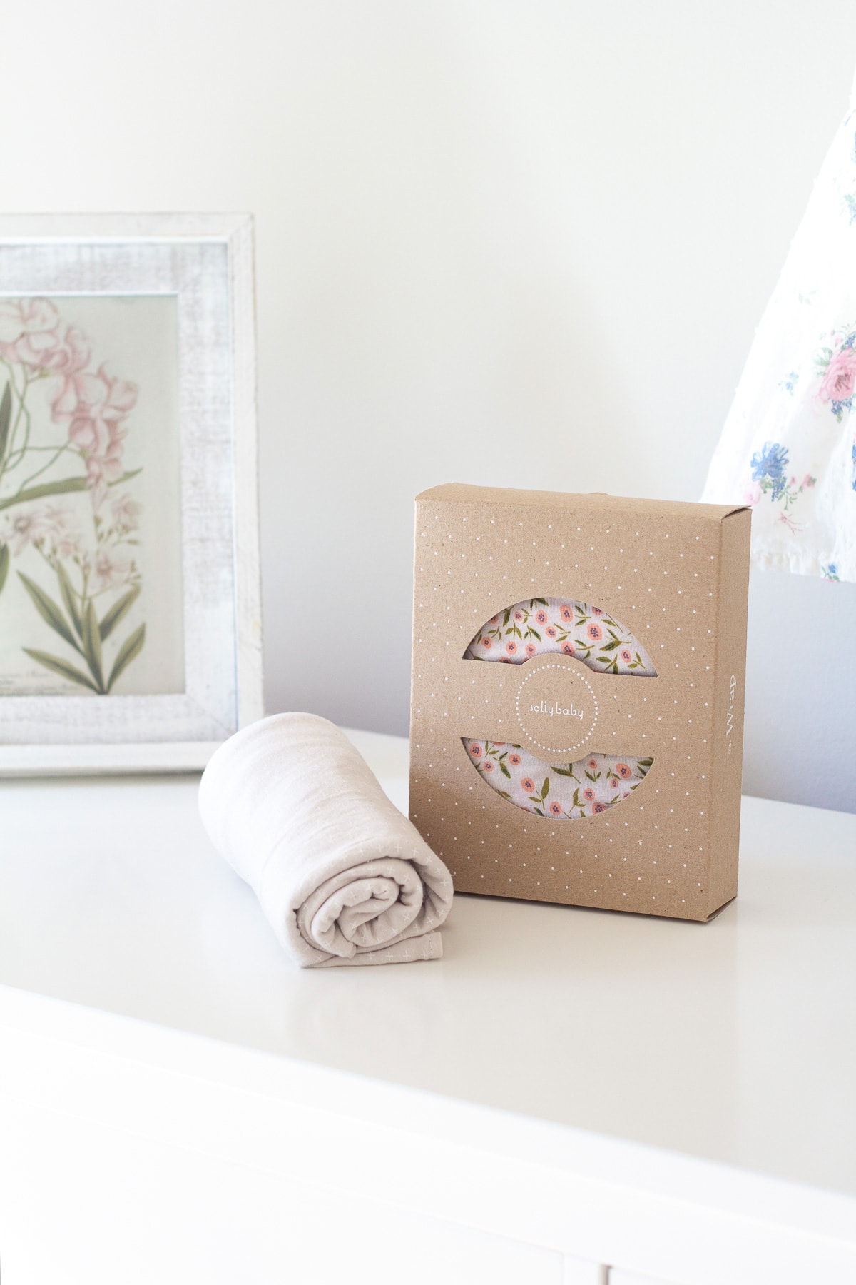 A Solly Swaddle blanket and a Solly Baby Wrap on a white dresser.