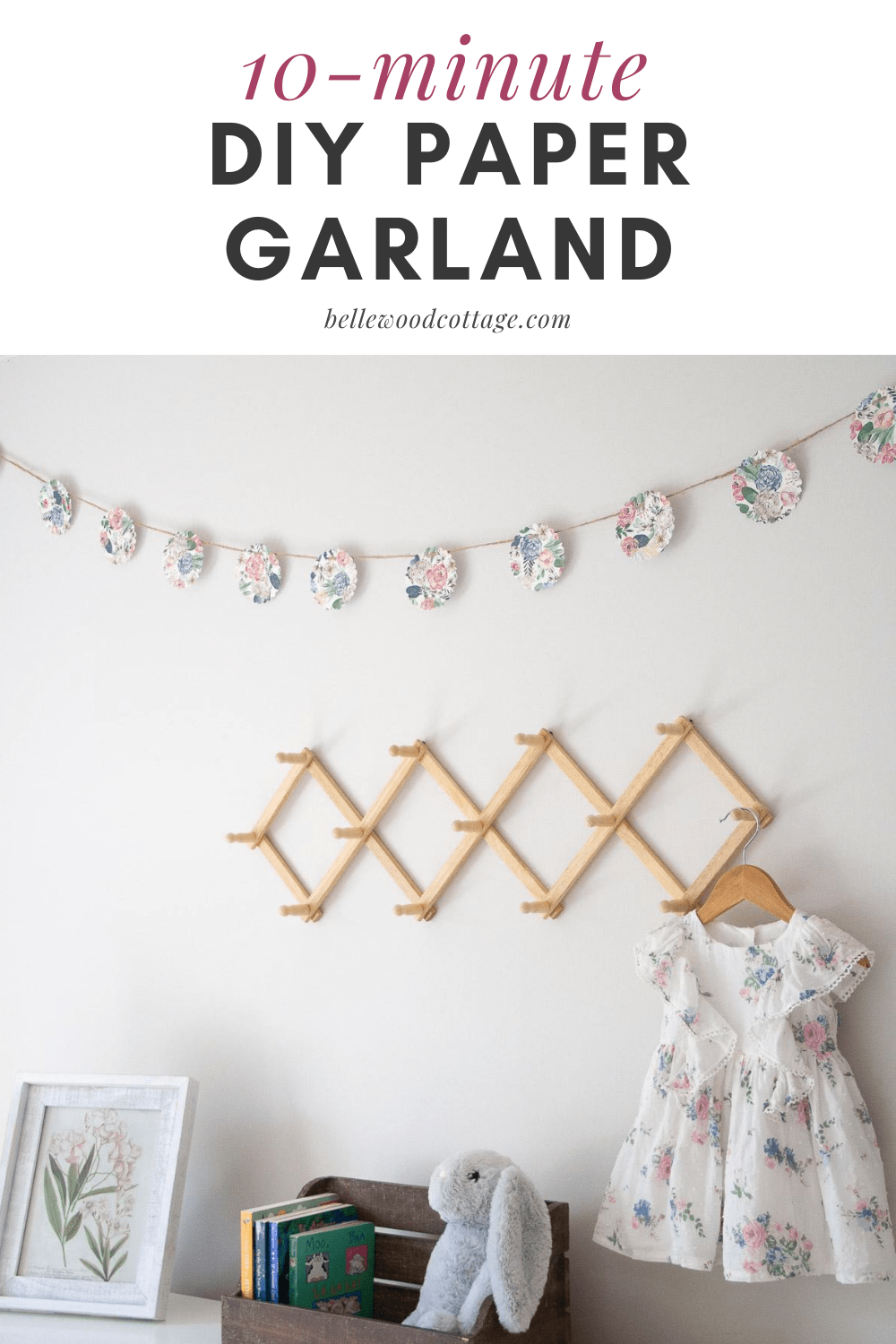 A diy paper garland hanging on the wall above other home decor like books and a peg rack.