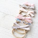 Seven bias tape hair bows on a wooden surface.