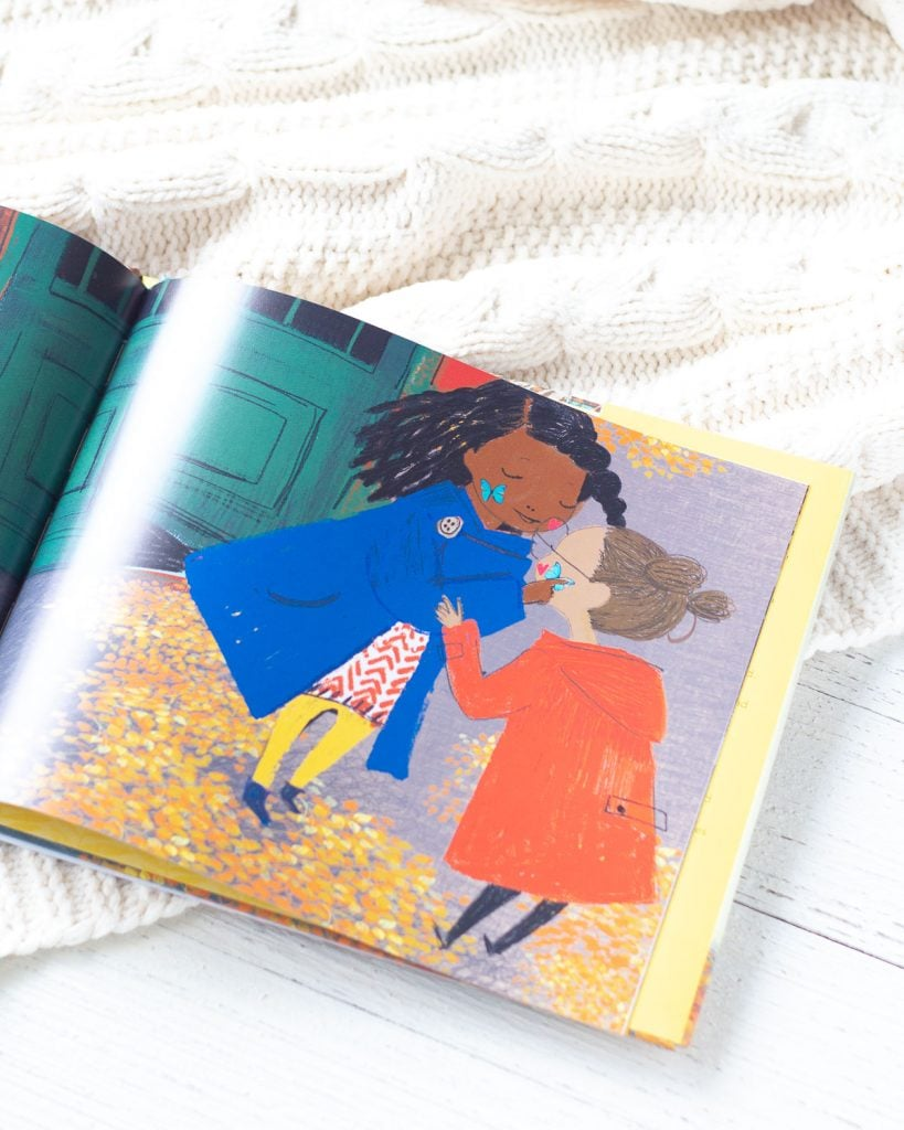 The inside pages of a picture book showing two young girls exchanging sparkly butterfly stickers.