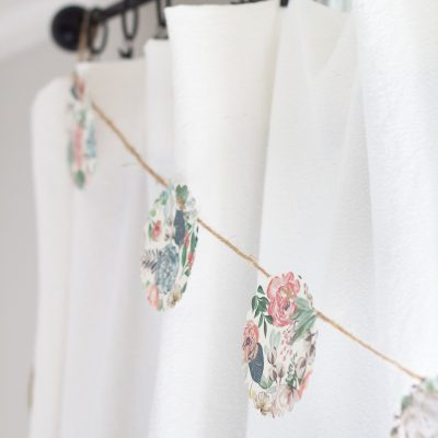 A paper garland hanging on a curtain rod.