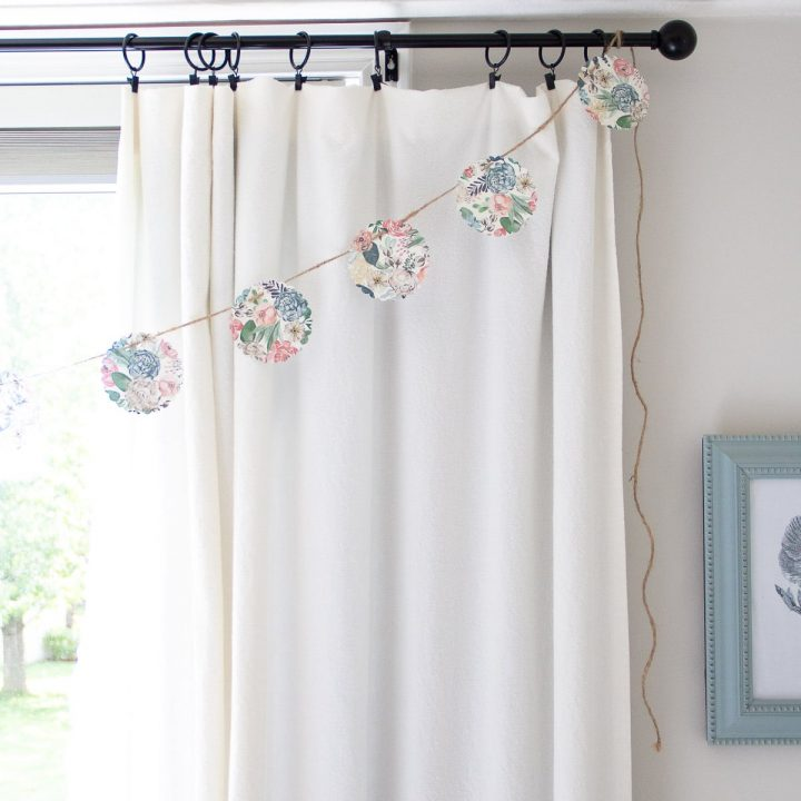 A DIY No-Sew Paper Garland hanging on a curtain rod.