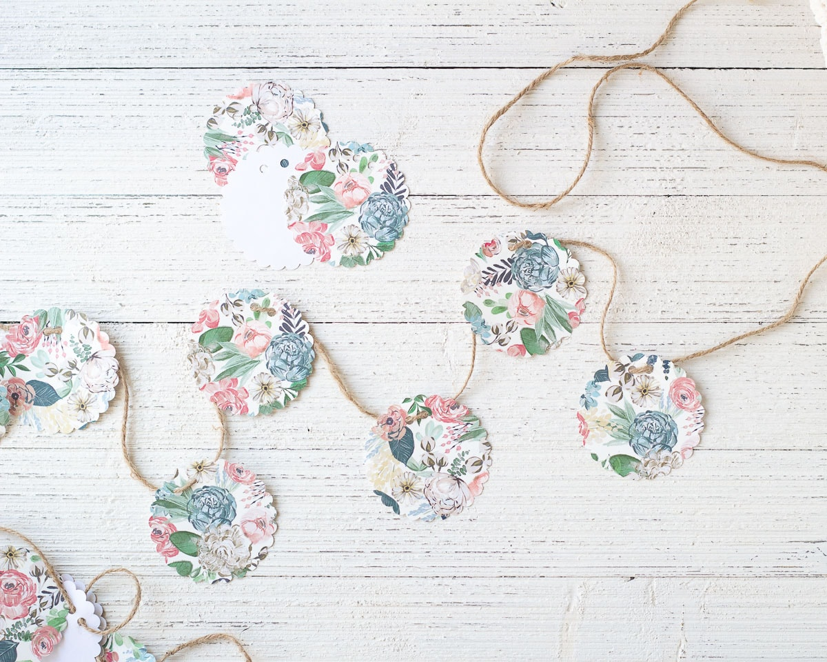 A paper garland made with scrapbook paper and twine on a wooden surface.