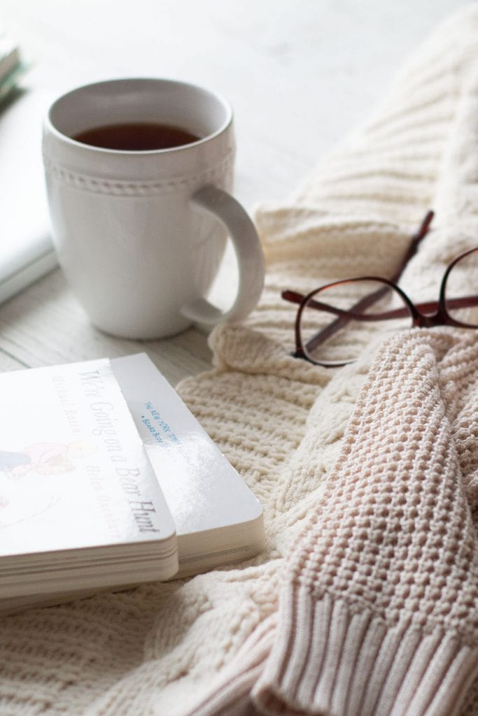 A mug of tea, glasses, books, and a fall sweater.