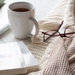 A white mug of tea alongside a cardigan sweater, glasses, and some board books.