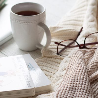A white mug of tea alongside a cardigan sweater, glasses, and some board books.