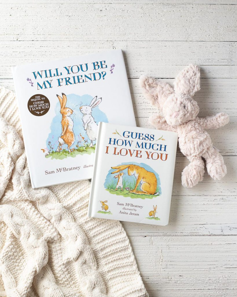 Children's books: Will You Be My Friend and Guess How Much I Love You by Sam McBratney and illustrated by Anita Jeram on a wooden surface.