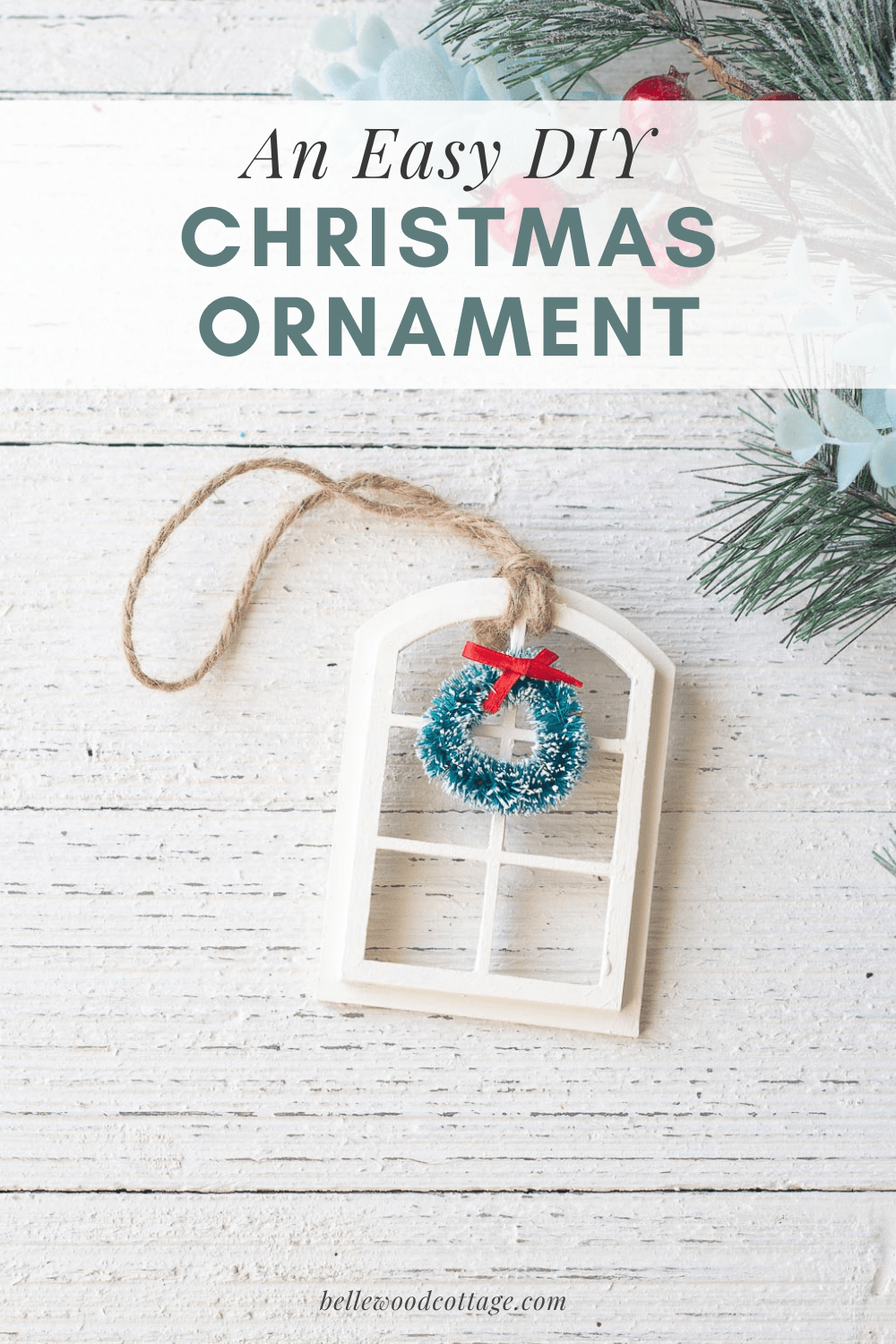 A DIY Christmas ornament (a miniature window with a wreath) on a wooden surface.