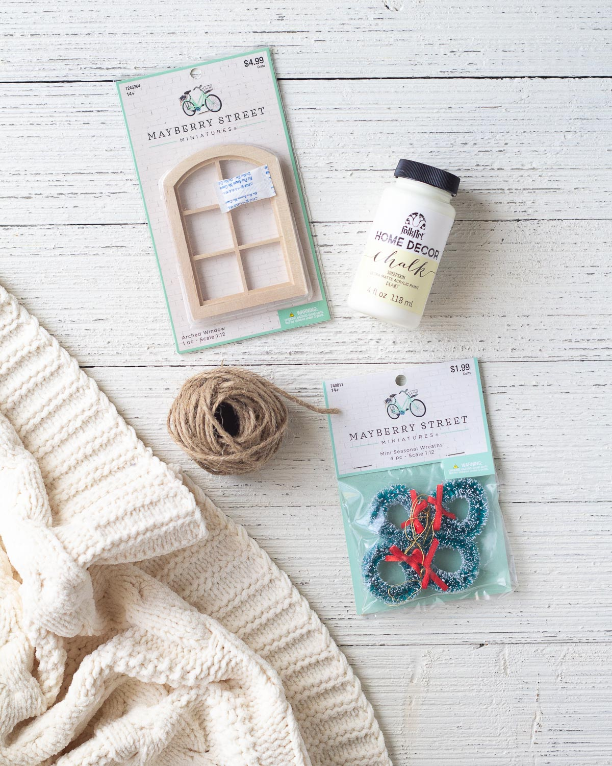 Supplies for a DIY Christmas ornament including chalk style paint, mini wreaths, a dollhouse window, and twine.