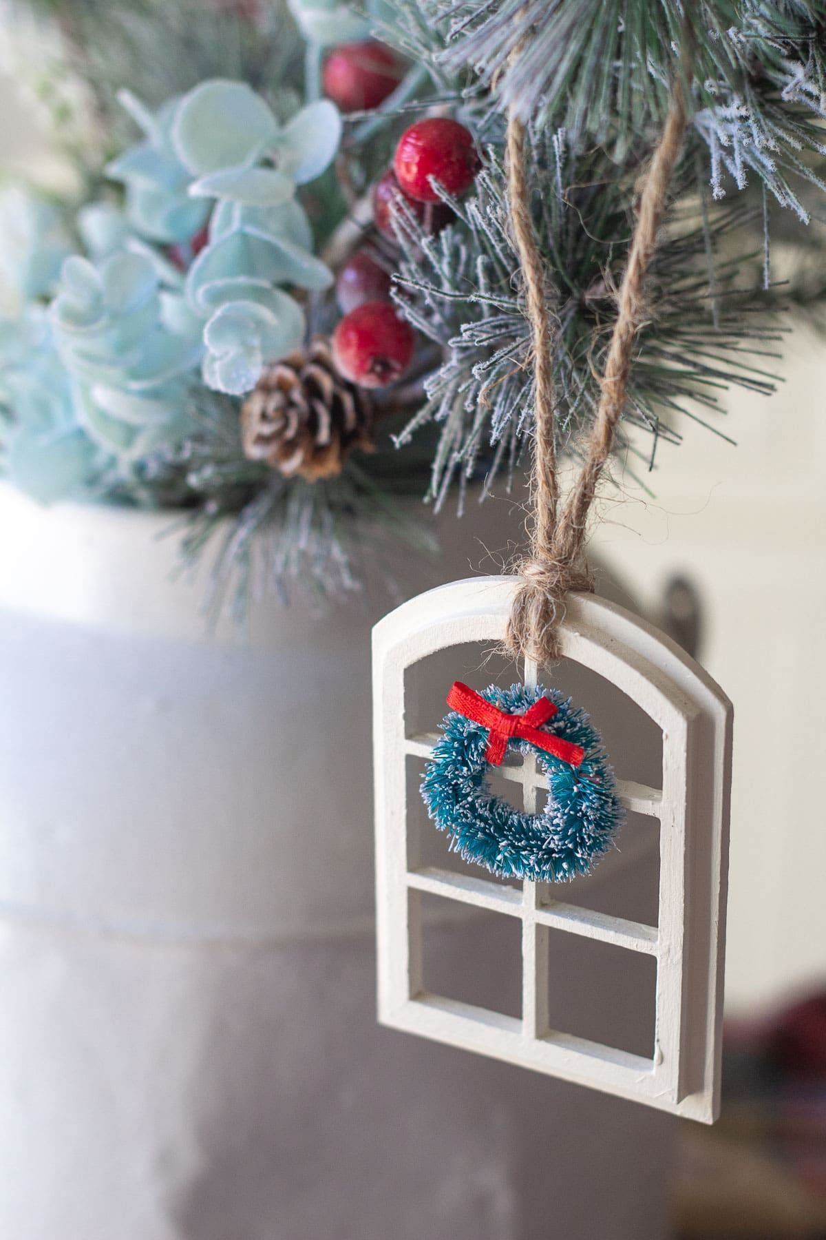 A handmade Christmas window ornament hanging from a decorative pine bough.