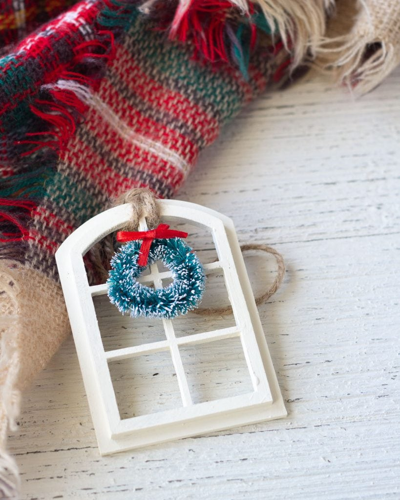 A Christmas ornament that is a window with a wreath in miniature displayed on a wooden surface.