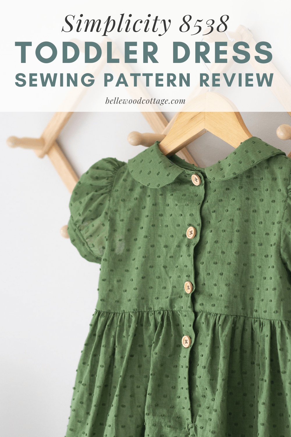A green handmade toddler dress with wooden buttons and a Peter Pan collar hanging on a wooden hanger.