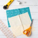 French seams on fabric samples and sewing supplies on a wooden background.