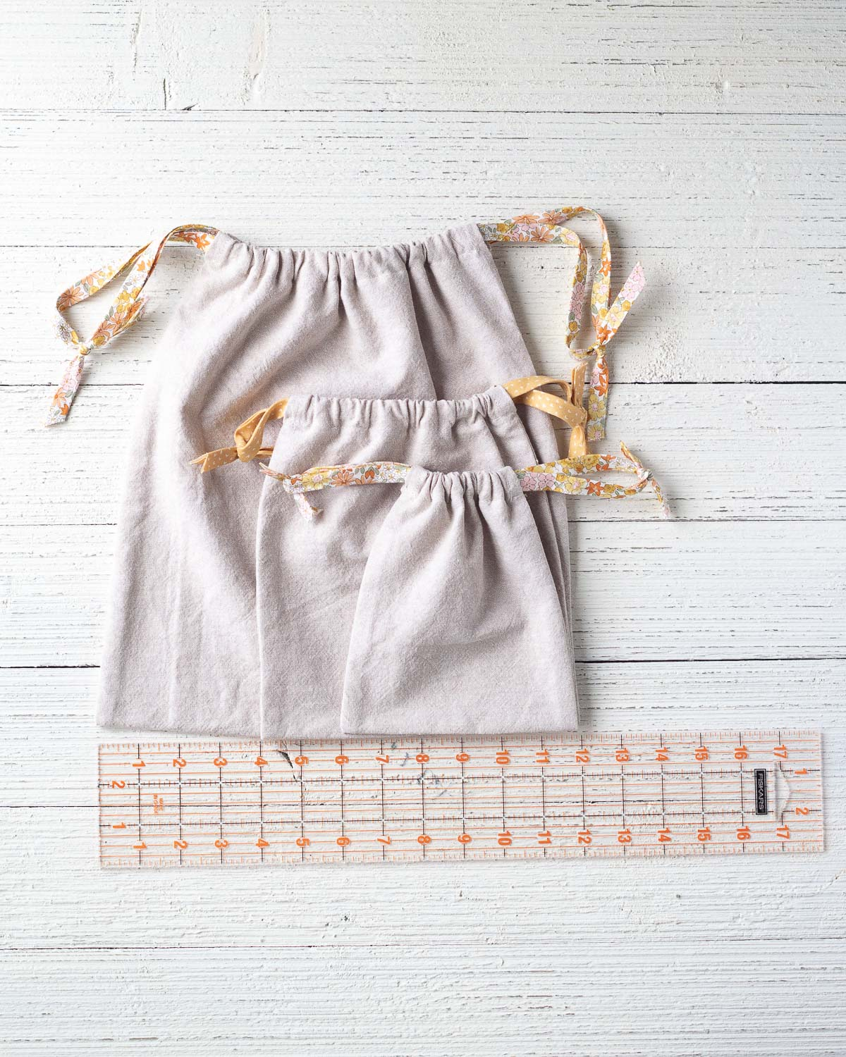 Three drawstring bags on a wooden surface with a ruler.