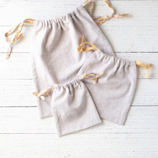 Three handmade drawstring bags made of linen and handmade bias tape arranged on a wooden surface.