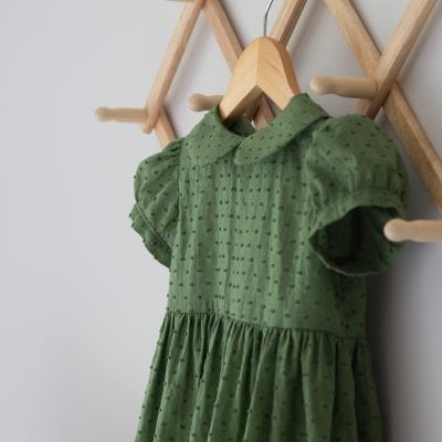 A toddler dress hanging on a wooden hanger.