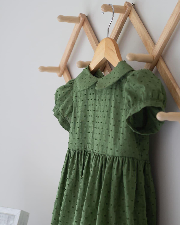 A toddler dress hanging on a wooden hanger.