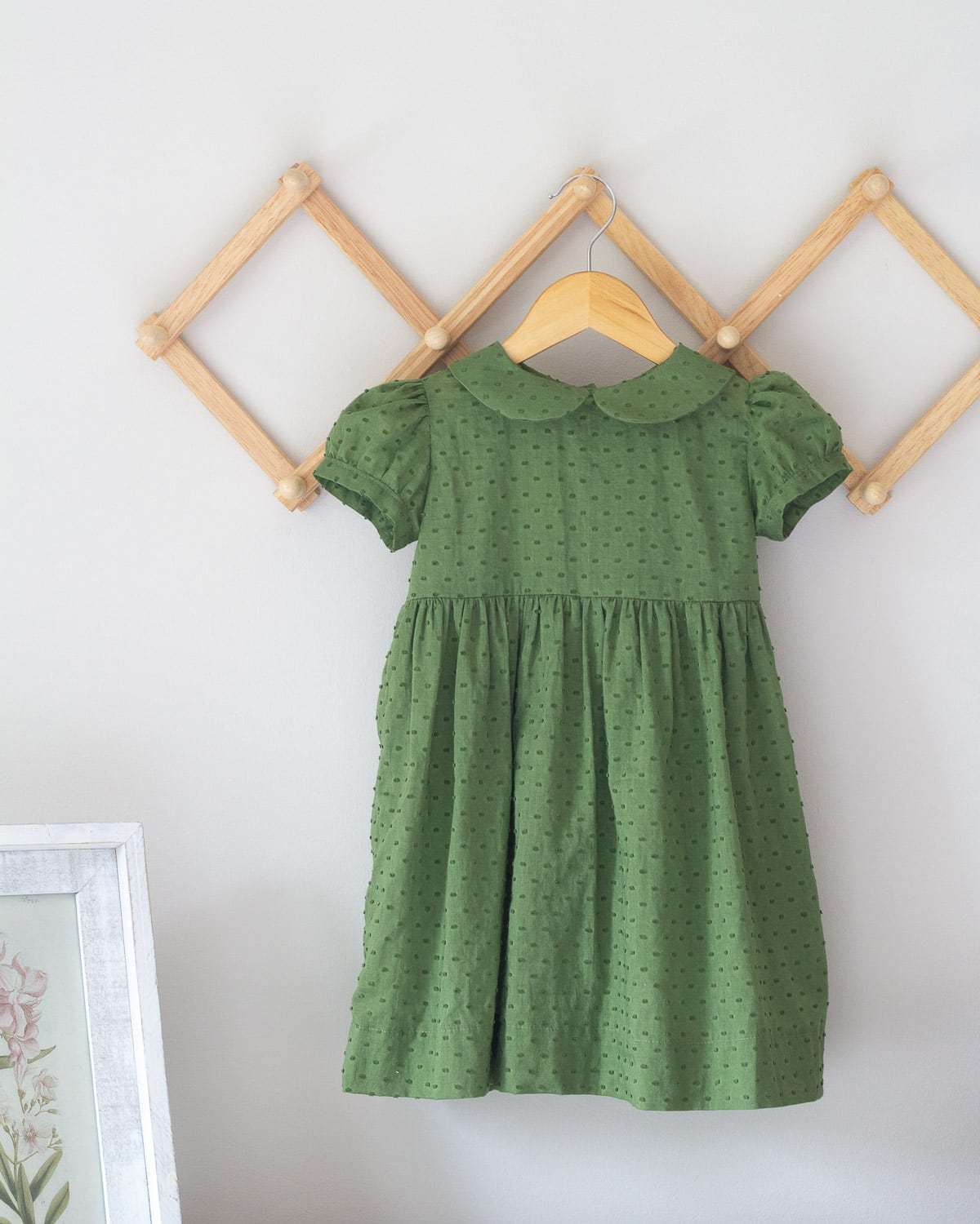A green toddler dress with a peter pan collar hanging on a wooden hanger.