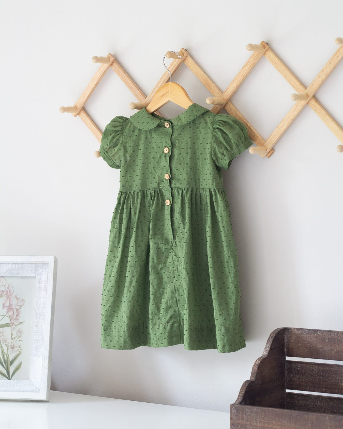 The back of a green toddler dress with wooden buttons.
