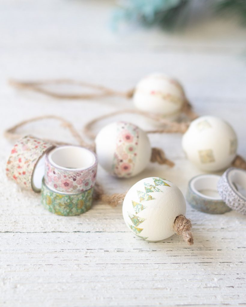 Spools of washi tape and decorated Christmas ornaments on a wooden surface.