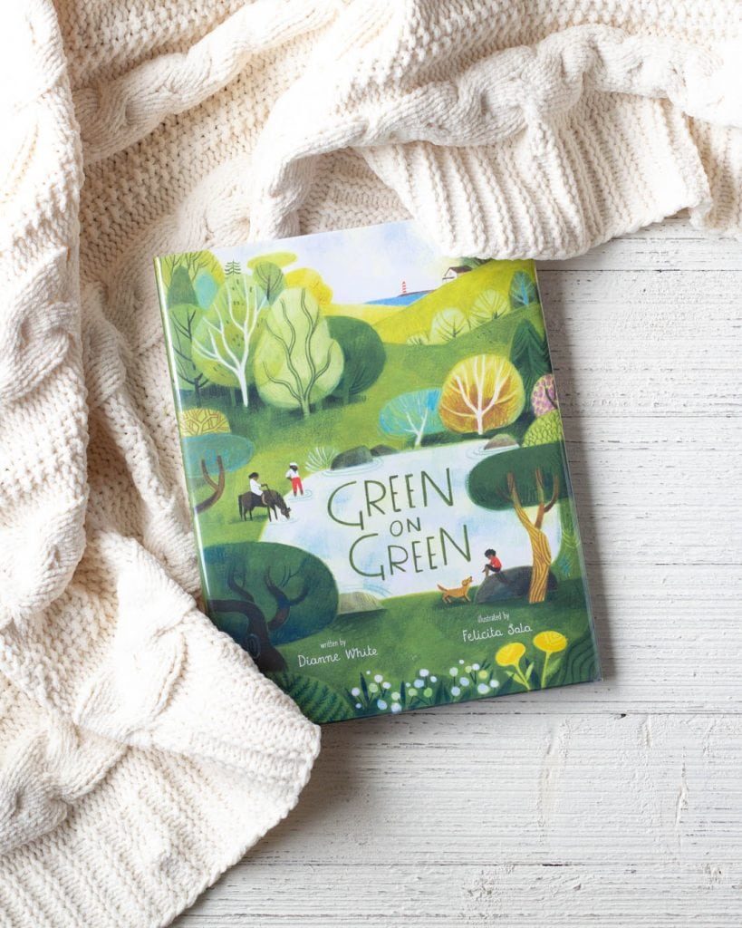 "A children's picture book titled, ""Green on Green"", on a wooden surface."