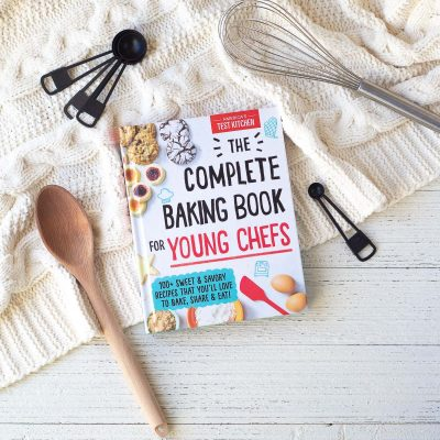 The Complete Baking Book for Young Chefs (a cookbook) on a wooden surface.