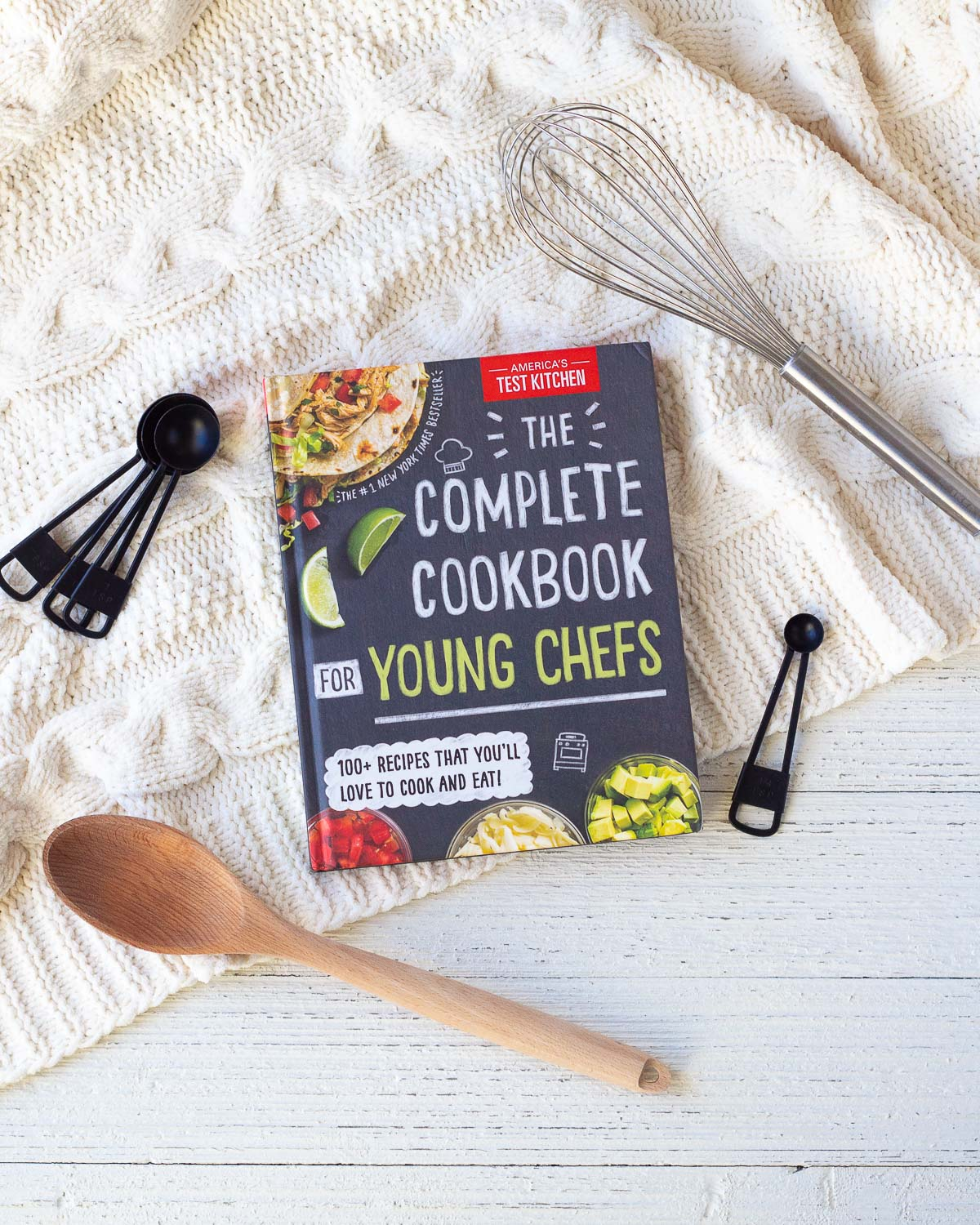 A children's cookbook on a wooden surface surrounded by cooking utensils.