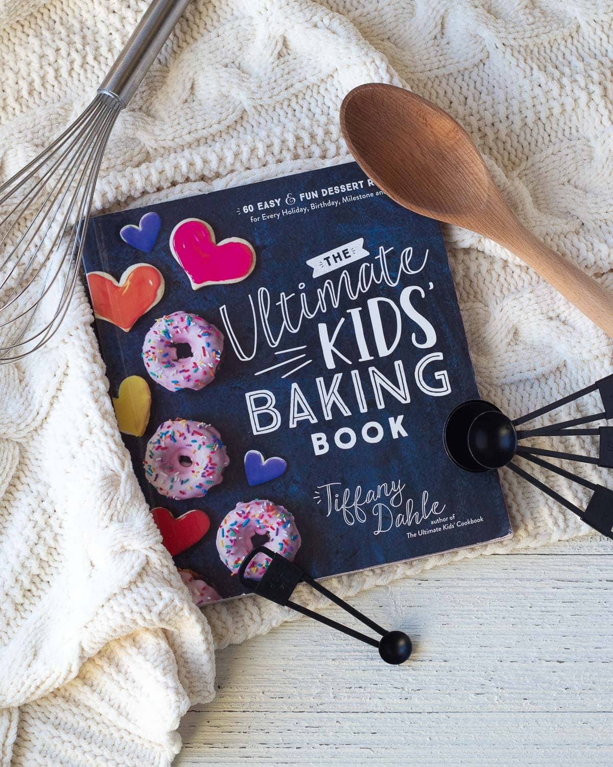 A baking book for kids surrounded by teaspoons and a wooden spoon.