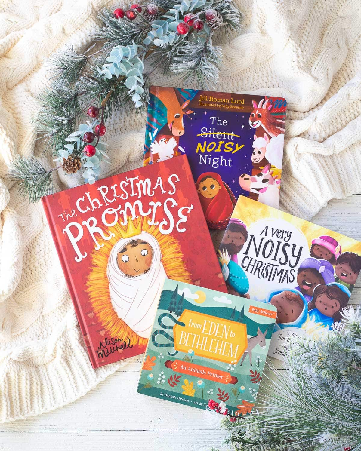 Several Christian Nativity books for reading to kids and babies at Christmas on a wooden surface with faux pine branches around them.