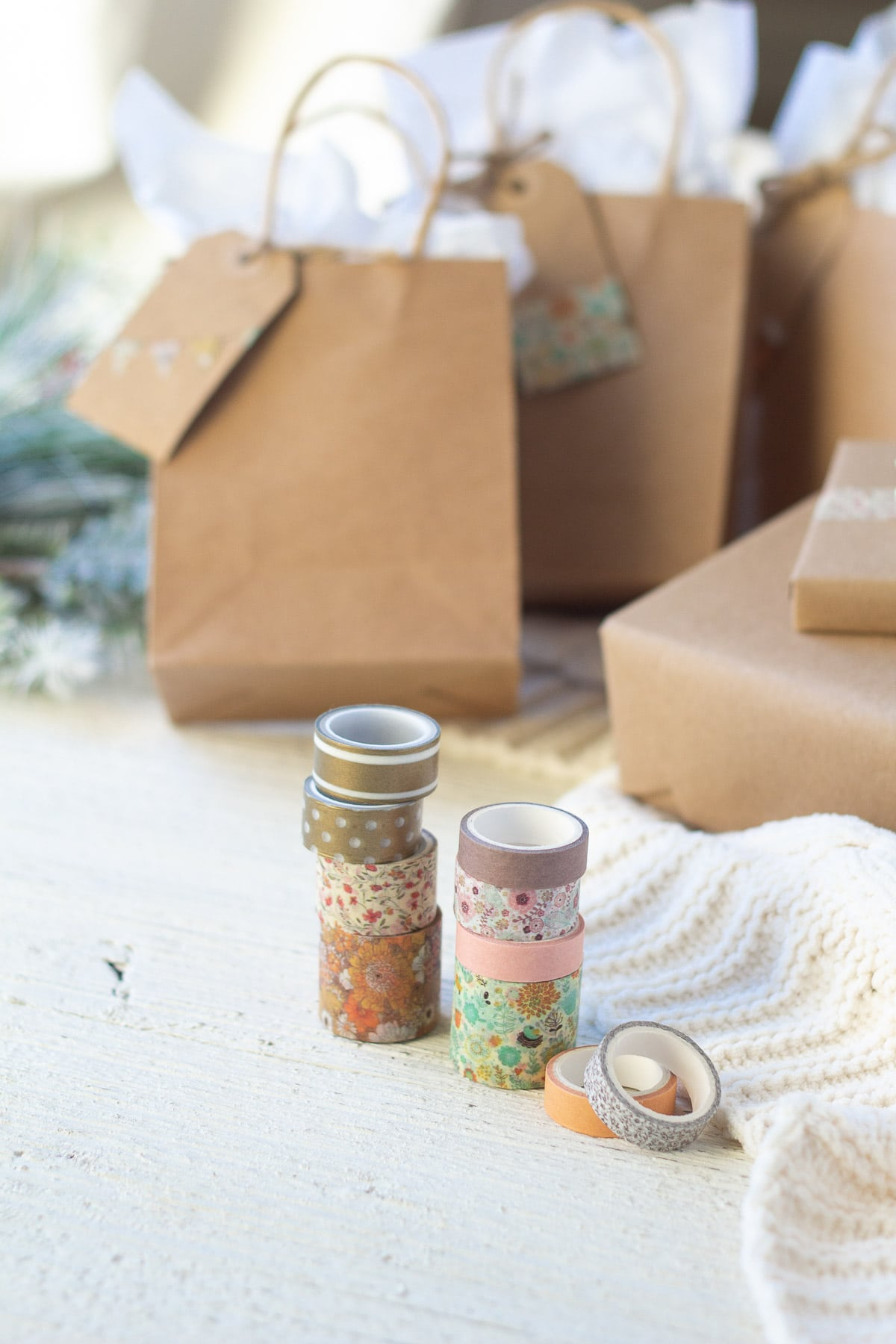 A stack of washi tape rolls in front of wrapped gifts.