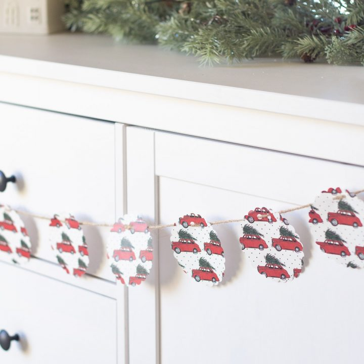 A simple scrapbook paper garland used as a Christmas decoration across a white IKEA sideboard.