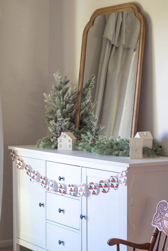 A white sideboard decorated for Christmas with a mirror, faux pine garlands, mini Christmas trees, and a paper garland.