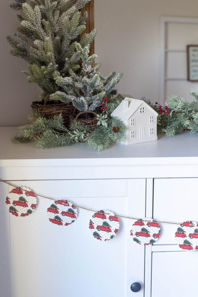 A white sideboard decorated for Christmas with faux pine garlands, white ceramic houses, mini Christmas trees, and a paper garland.