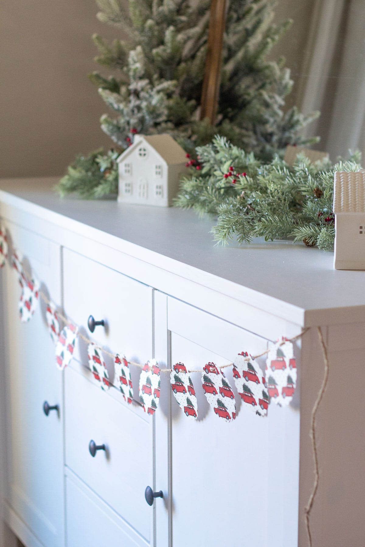 A Christmas Garland made from scrapbook paper hanging across a white sideboard.