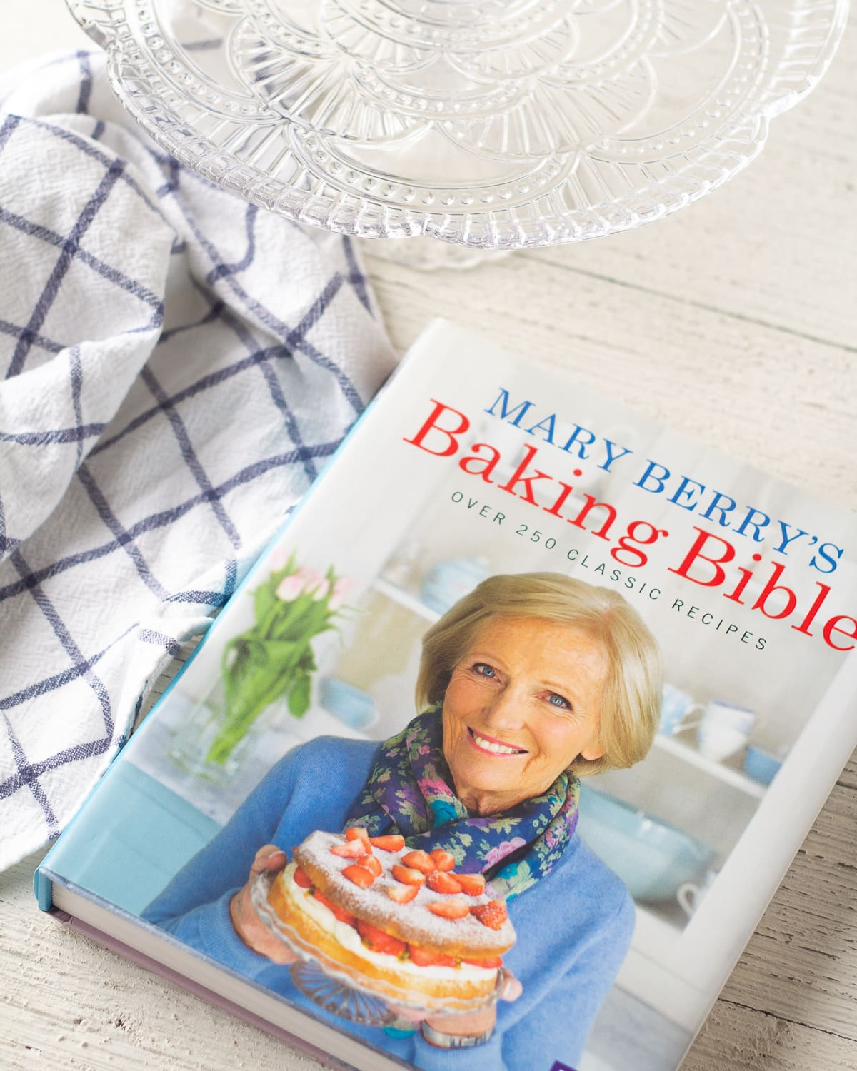 A Mary Berry cookbook, cake stand, and IKEA towel on a wooden surface.