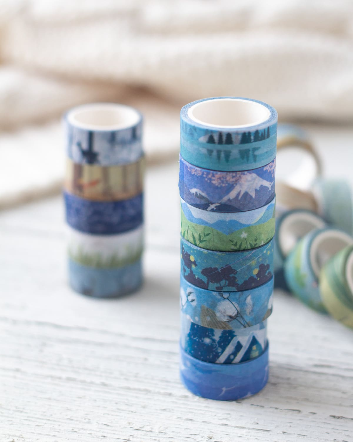 Washi tape with landscape designs stacked on a wooden surface.