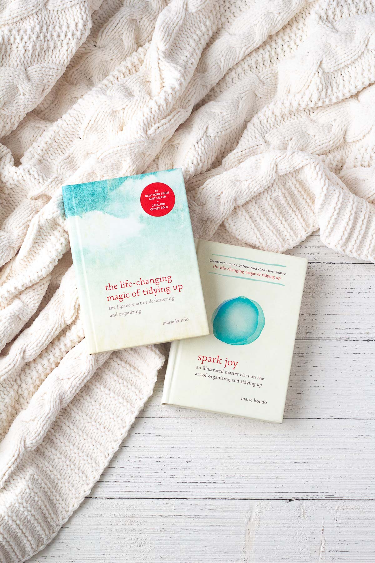 Marie Kondo's books (which provide decluttering tips) on a knit blanket and wooden surface.