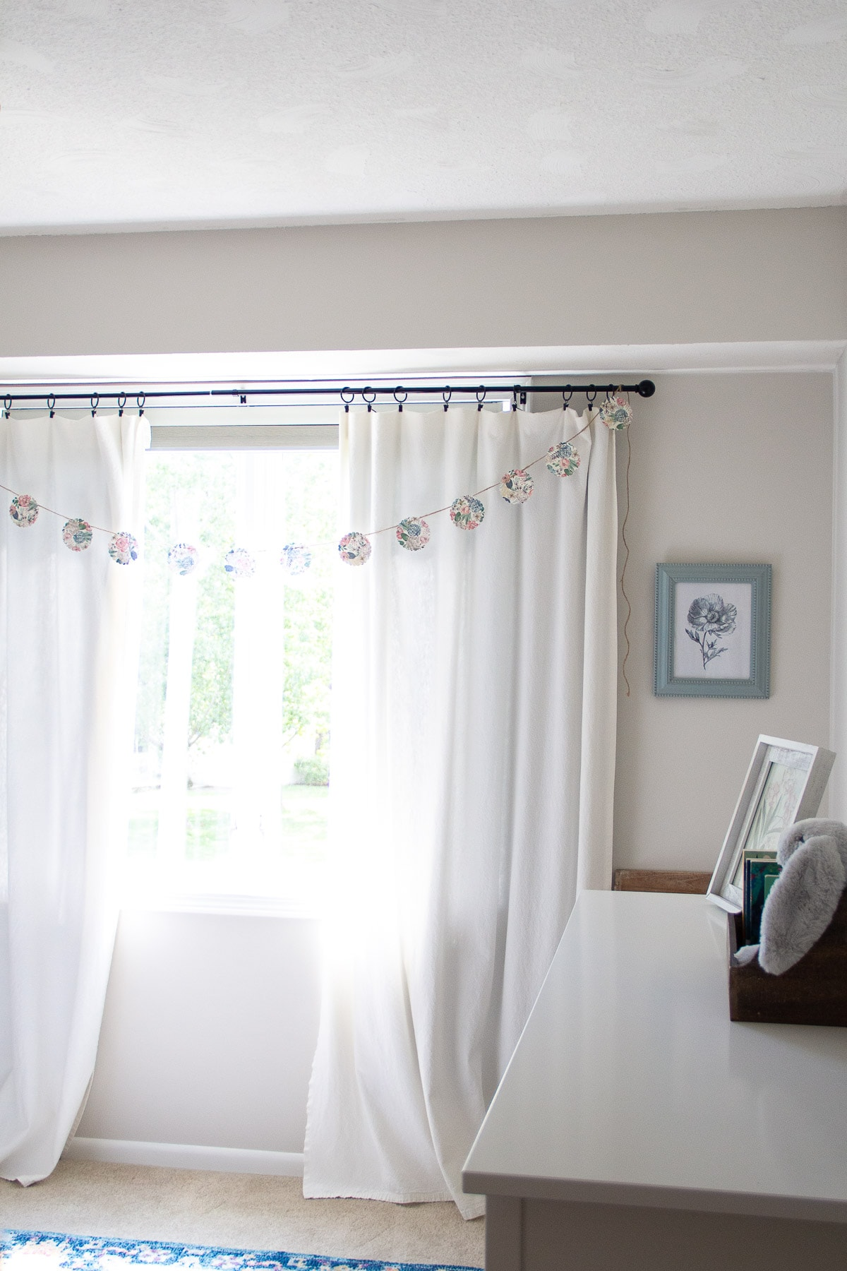 Bleached drop cloth curtains hanging in a nursery.