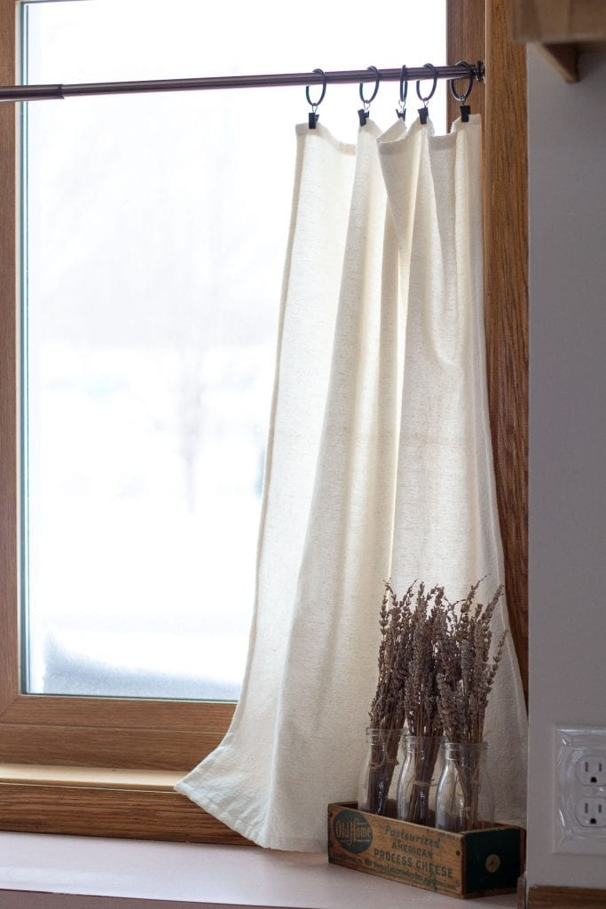 Drop cloth curtains in a kitchen window.