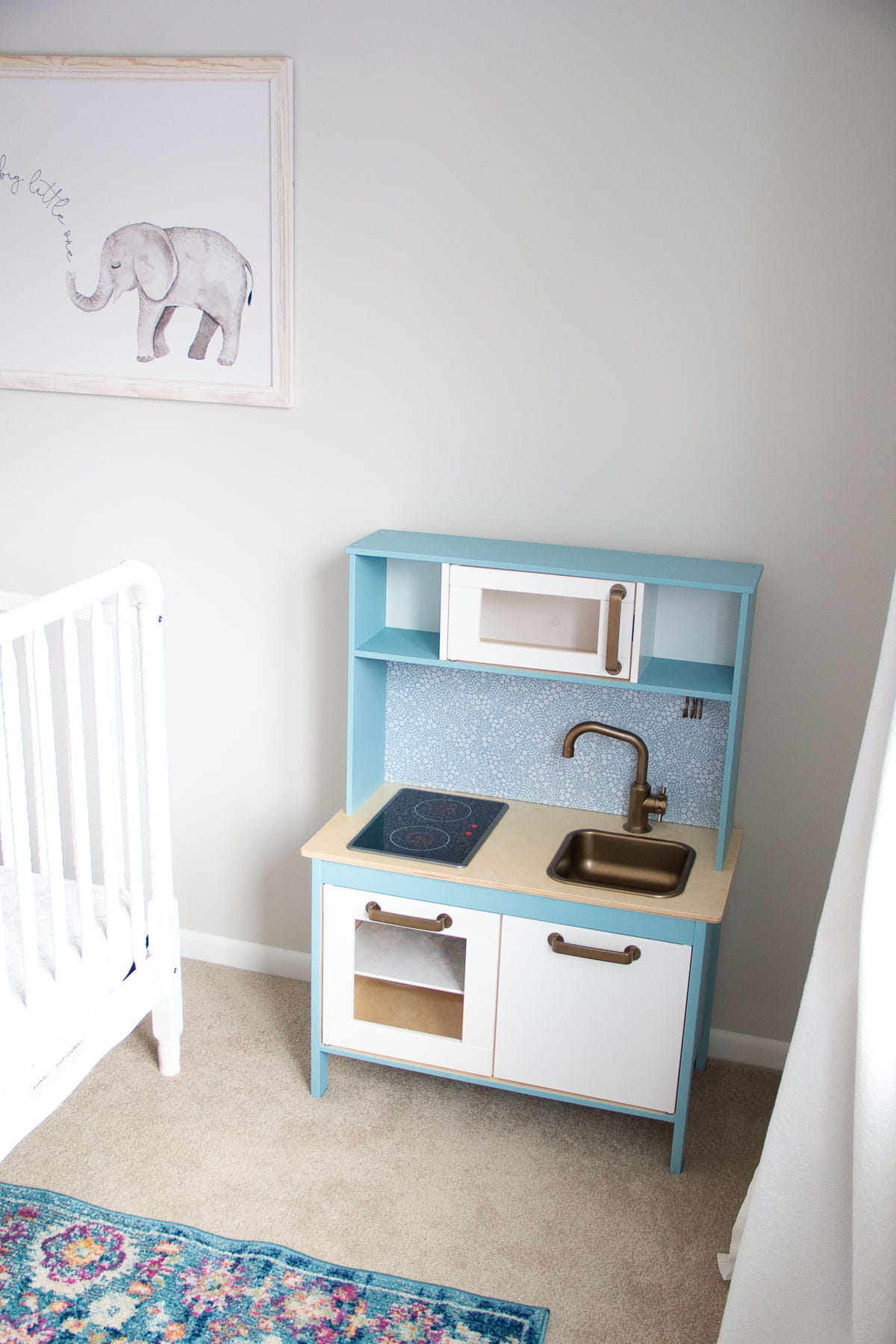 An IKEA play kitchen hack painted with blue chalk style paint.