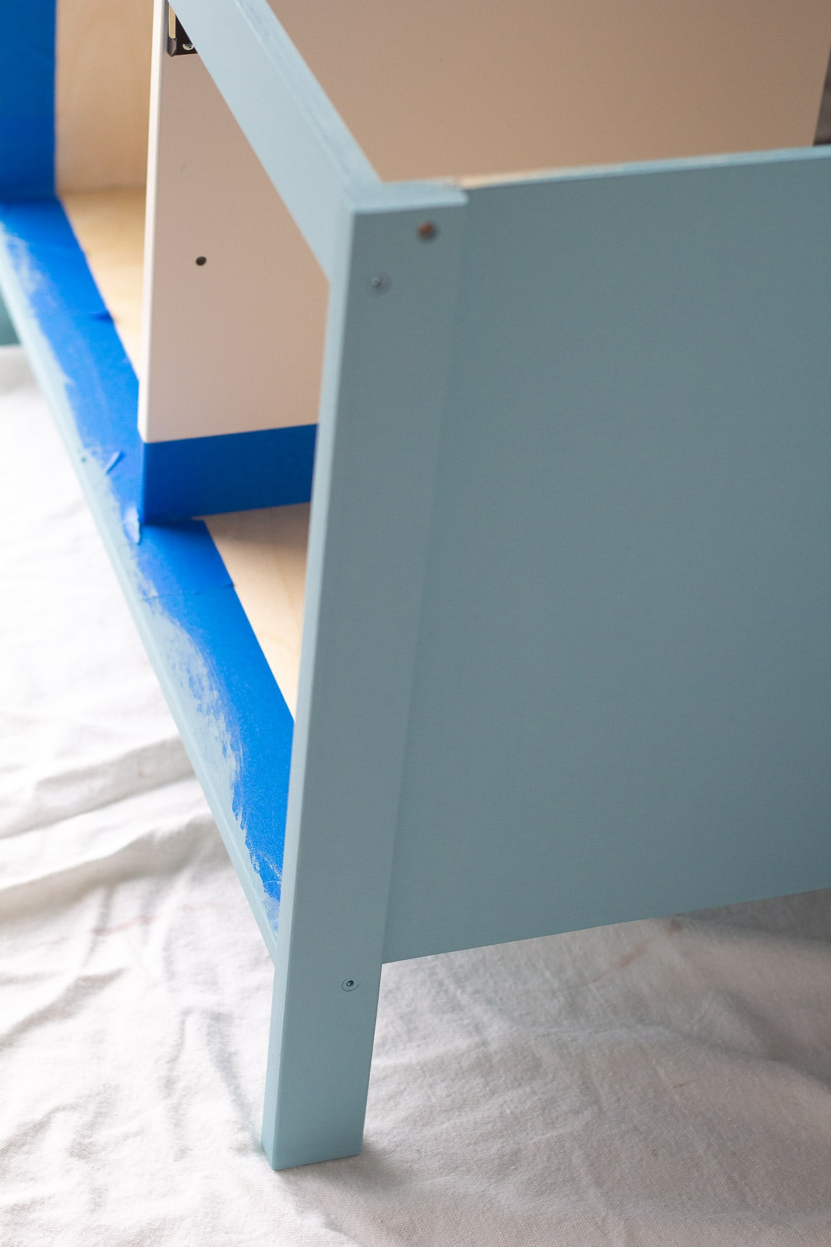 Painting an IKEA play kitchen with blue paint.