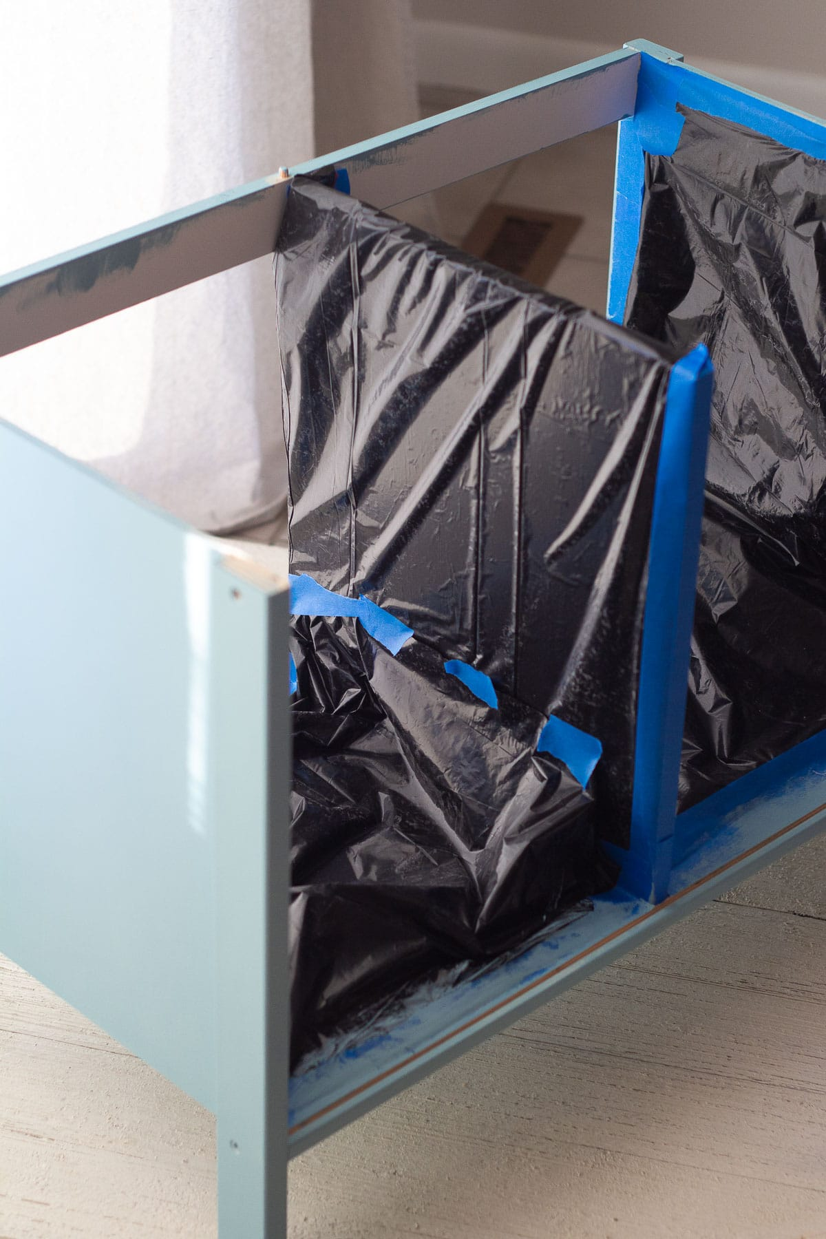 Taping off and masking an IKEA play kitchen for spray painting.