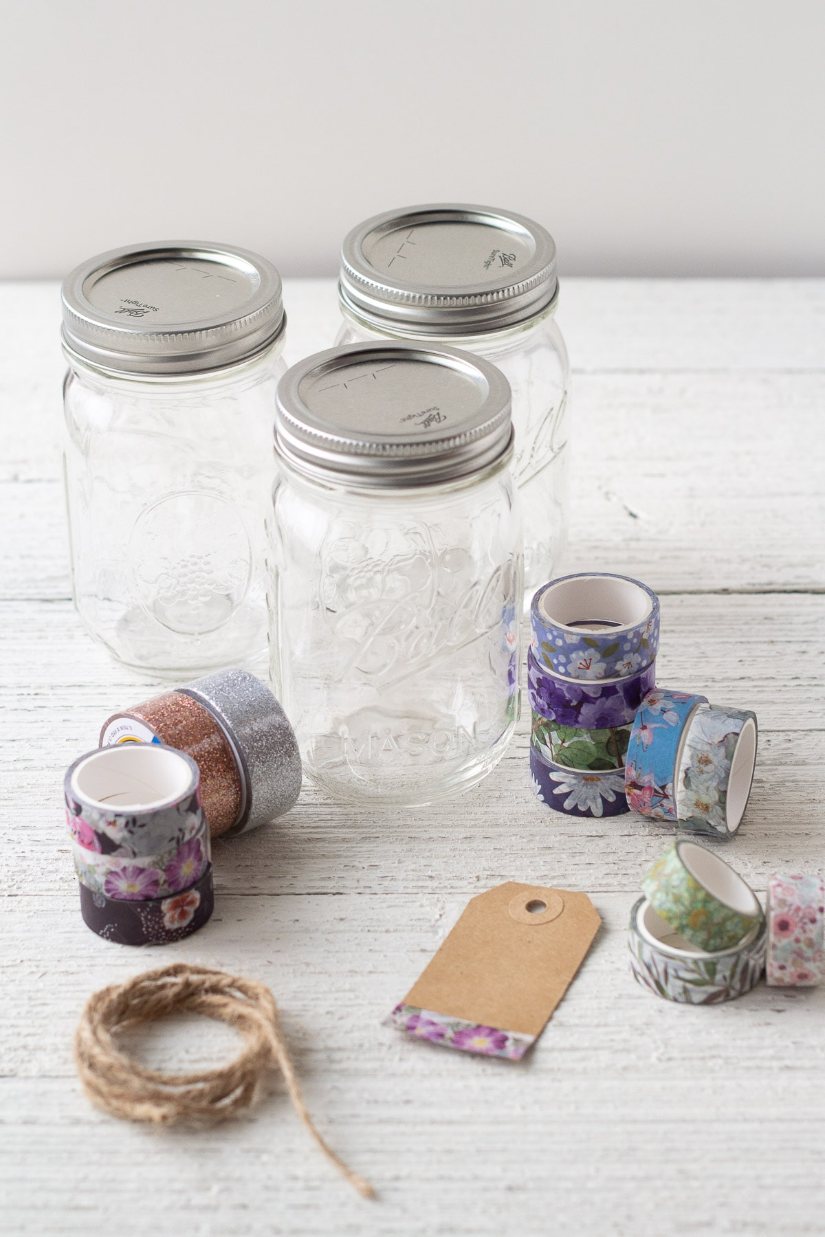 Mason jars, washi tape, twine, and a gift tag on a wooden surface.