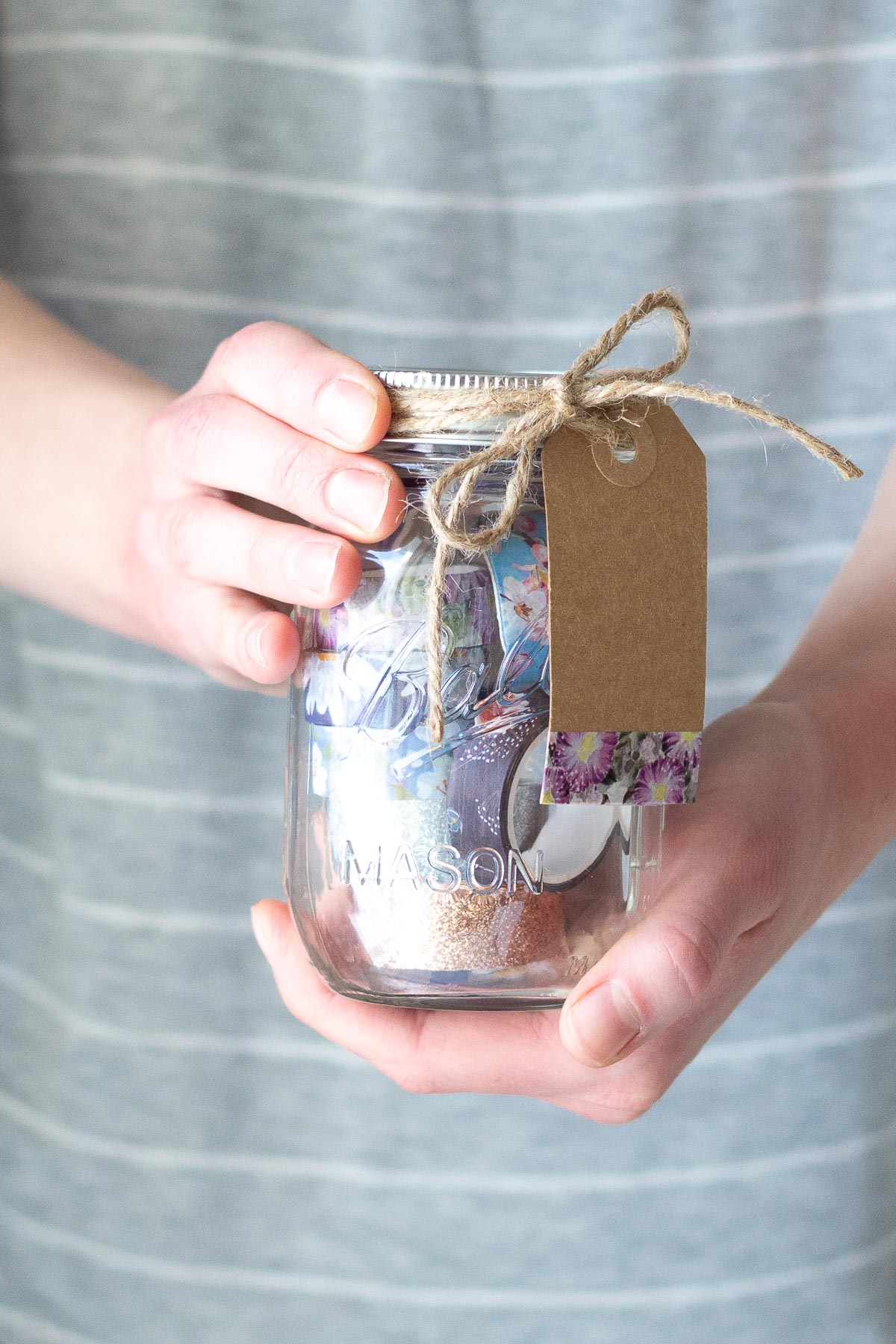 Holding a Washi Tape Mason Jar Gift Idea filled with colorful washi tape.
