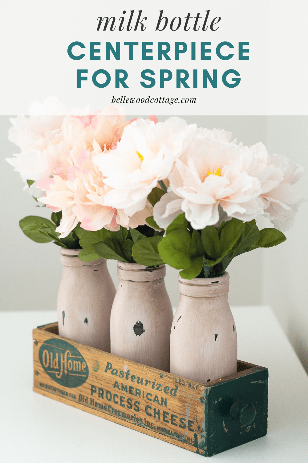 "Painted milk bottles in a vintage cheese box with the words, ""Milk Bottle Centerpiece for Spring"""