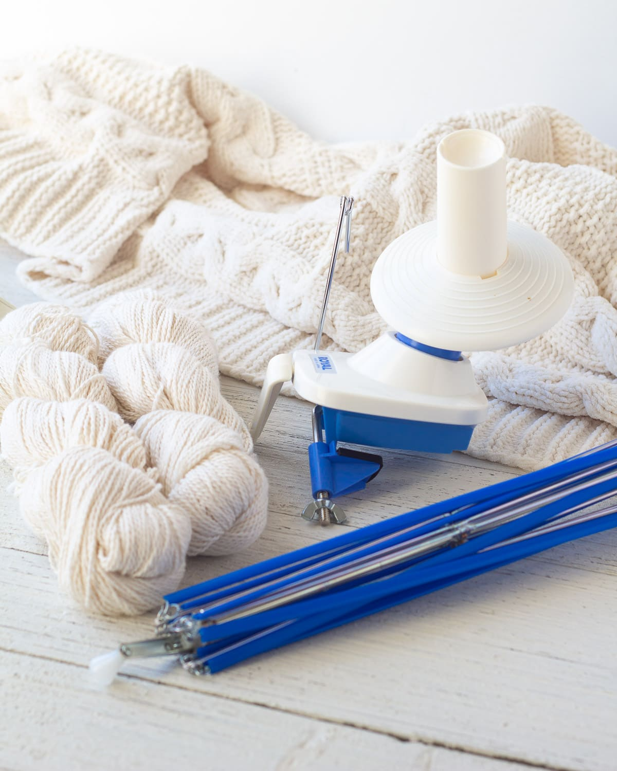 A swift, ball winder, and white yarn for knitting.