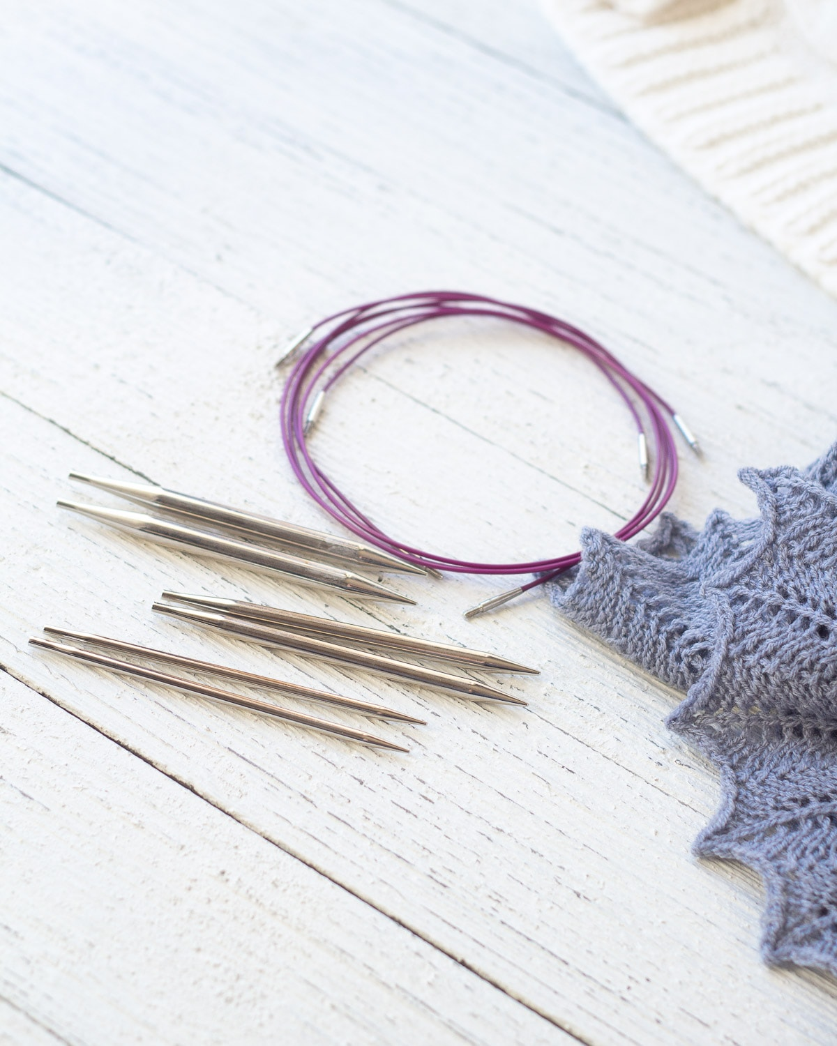 Gift idea for new knitters: Knit Picks Nickel Interchangeable Knitting Needle Set on a wooden surface.