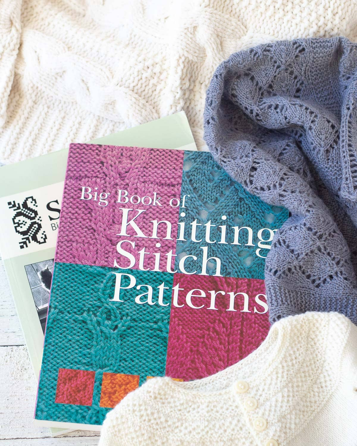 Knitting books surrounded by handknit items.