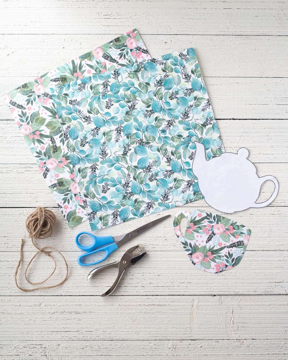 Teapot template, scrapbook paper, scissors, hole punch, and twine on a wooden surface.